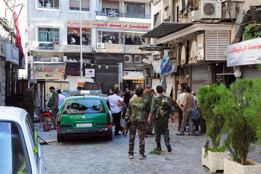 In this photo released by the Syrian official news agency SANA, Syrian army soldiers stand guard at a scene of two explosions in the central district of Marjeh, Damascus, Syria, Tuesday, June 11, 2013. State TV said the blasts were caused by suicide bombers, while activists said they were bombs planted there in advance. (AP Photo/SANA)