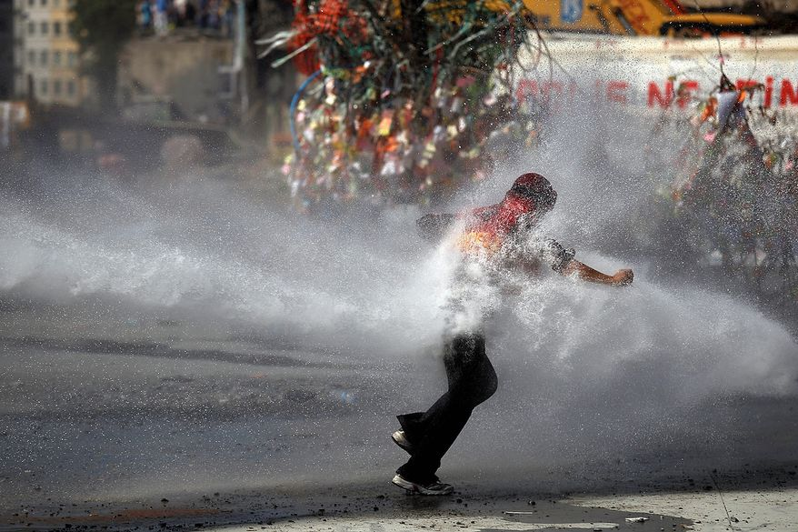 A protester tries to remain standing against the force of a police water cannon during clashes in Taksim Square in Istanbul on Tuesday, June 11, 2013. Hundreds of police in riot gear forced through barricades and pushed many of the protesters who had occupied the square for more than a week into a nearby park. (AP Photo/Kostas Tsironis)