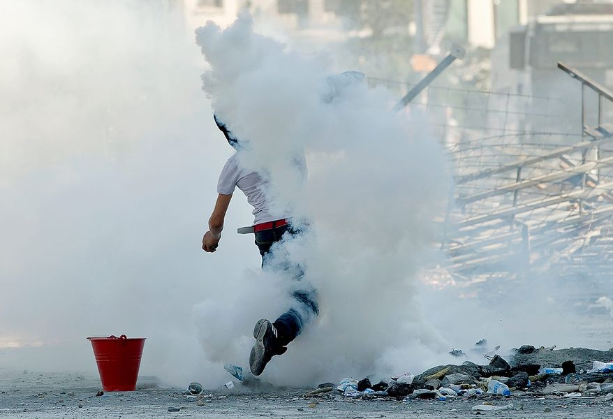 A protester throws back a tear gas canister toward riot police during clashes in Taksim Square in Istanbul on Tuesday, June 11, 2013. Hundreds of police in riot gear forced through barricades and pushed many of the protesters who had occupied the square for more than a week into a nearby park. (AP Photo/Vadim Ghirda)