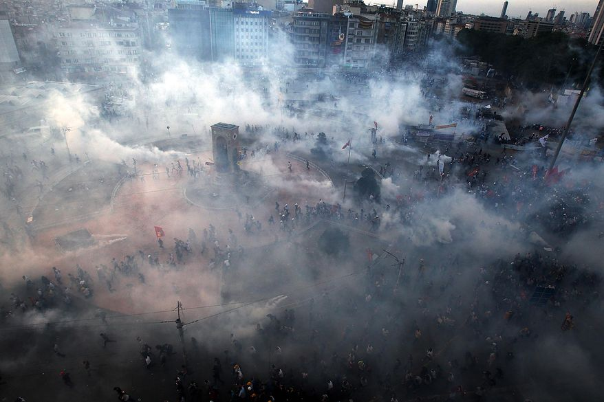 Protesters run to avoid tear gas during clashes at Taksim Square in Istanbul on Tuesday, June 11, 2013. Hundreds of riot police overran improvised barricades at the square and fired tear gas, rubber bullets and water cannon in running battles with protesters who have been occupying the area for more than a week. (AP Photo/Thanassis Stavrakis)
