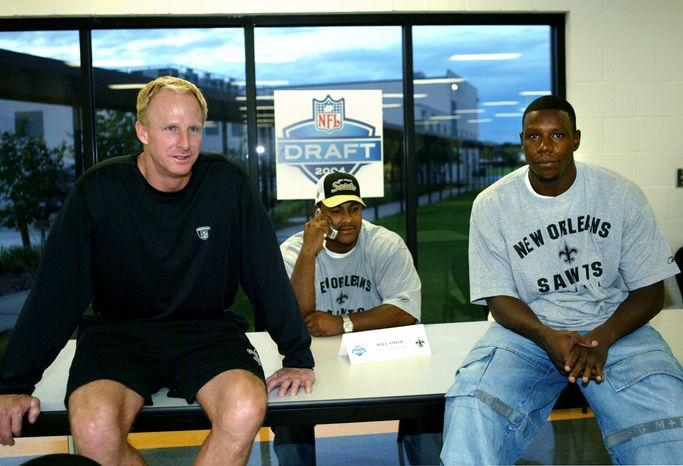 **FILE** New Orleans Saints coach Jim Haslett, left, and draft picks Devery Henderson, right, and Will Smith, center, gather for a press conference Friday, April 30, 2004, at Saints camp in Metairie, La. Smith is talking on a cell phone during a radio interview. (AP Photo/Judi Bottoni)