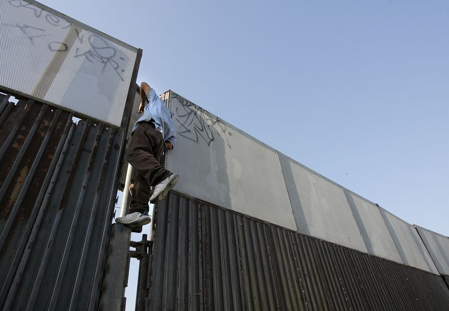 **FILE** An undocumented migrant, who refused to identify himself, clings to the border as he checks on the U.S. Border Patrol from the Mexico side of the United States-Mexico border in Tijuana, Mexico, on June 5, 2006. (Associated Press)