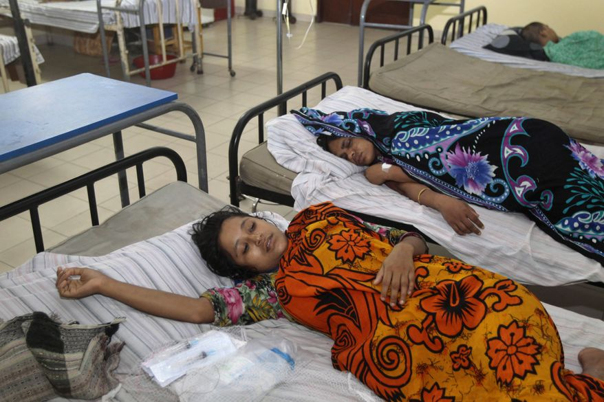 Bangladeshi garment workers who fell ill during their shifts at a sweater factory lie on beds at a hospital on the outskirts of Dhaka, Bangladesh, on June 6, 2013. About 450 garment workers fell ill at the Starlight Sweater Factory near Bangladesh's capital, due to possible water contamination. A building collapse near Dhaka in April killed 1,129 workers, injured others and highlighted the hazardous working conditions in thousands of garment factories in Bangladesh. (Associated Press)