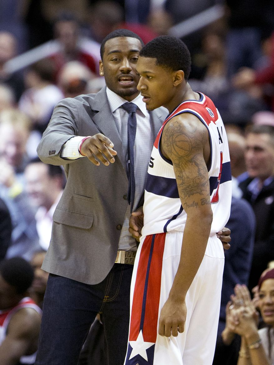 Washington Wizards Bradley Beal, right, listens to teammate John Wall during a timeout in the first overtime of an NBA basketball game against the Brooklyn Nets in Washington, Friday, Jan. 4, 2013. Brooklyn won 115-113 in a double overtime. (AP Photo/Manuel Balce Ceneta)