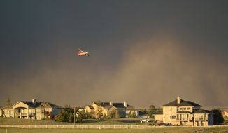 A slurry bomber flies over homes as it prepares to drop fire retardant on the Black Forest fire northeast of Colorado Springs, Colo., on Tuesday, June 11, 2013. The fire has consumed an estimated 7,500 acres and forced the evacuation of thousands of people. (AP Photo/BryanOller)