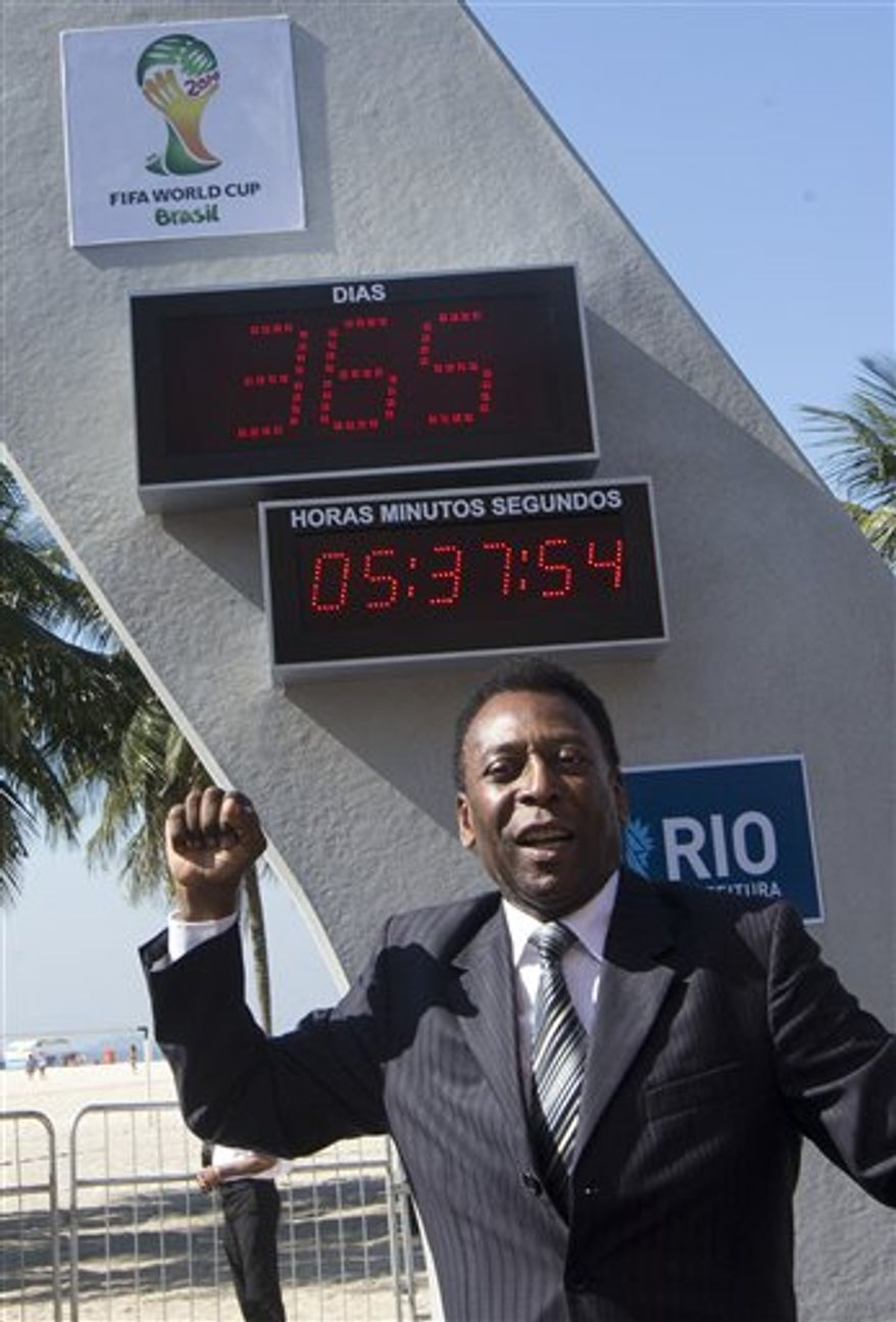 Brazilian football icon Pele cheers during the unveiling of the Hublot Countdown Clock designed by the late architect Oscar Niemeyer, at the Copacabana beach in Rio de Janeiro, Brazil, Wednesday, June 12, 2013. The event marks the start of the one-year countdown to the opening 2014 World Cup game in Brazil. (AP Photo/Silvia Izquierdo)