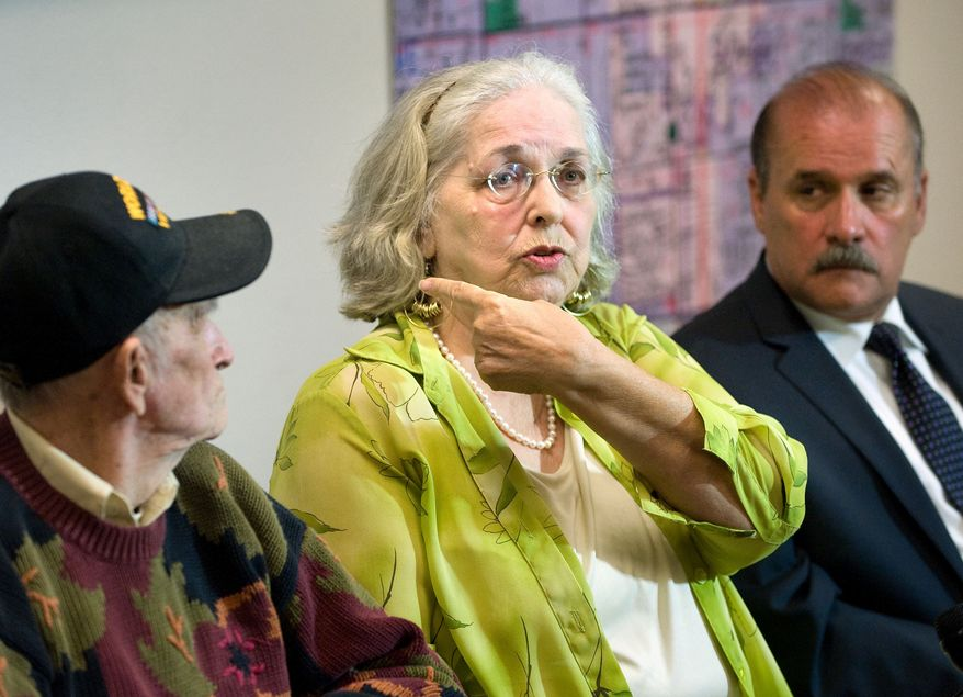 Jan Cooper, 72, talks to the media as her husband Bob, 85, left, and OC Sheriff's spokesman Jim Amormino listen during a news conference at the Sheriff's Department station in Stanton on Tuesday, June 11, 2013. Jan Cooper showed where the Sheriff's estimated the bullet traveled, based on the size of the suspect and the damage to her sliding glass door, when she scared off an intruder at her home in unincorporated Anaheim on Sunday, June 9, by firing a shot from her .357 Magnum during the attempted break-in. (AP Photo/The Orange County Register, Paul Bersebach)