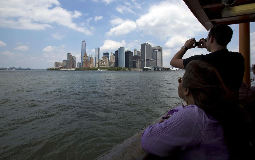 Passengers view lower Manhattan from the Staten Island Ferry while crossing New York's Upper Bay on Tuesday, June 11, 2013. Giant removable floodwalls would be erected around lower Manhattan, and levees, gates and other defenses would be built elsewhere around the city under a nearly $20 billion plan proposed by Mayor Michael R. Bloomberg to protect the city from storms and the effects of global warming. (AP Photo/Richard Drew)