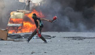 A man runs carrying fire extinguishers past a burning van during clashes at the Taksim Square in Istanbul Tuesday, June 11, 2013. Hundreds of police in riot gear forced through barricades in the square early Tuesday, pushing many of the protesters who had occupied the square for more than a week into a nearby park. (AP Photo/Vadim Ghirda)