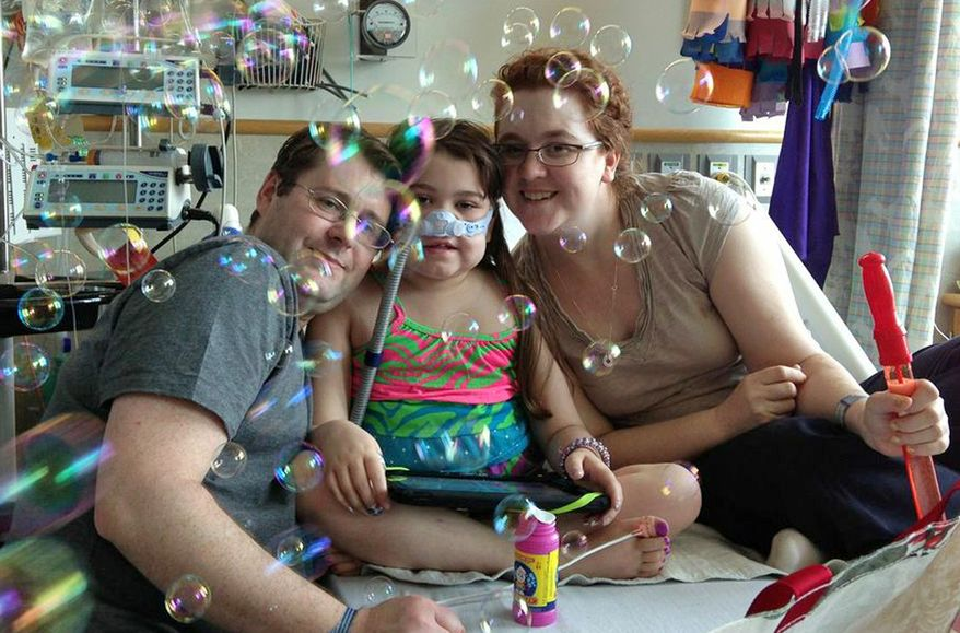 **FILE** In this May 30, 2013, file photo provided by the Murnaghan family, Sarah Murnaghan (center), celebrates the 100th day of her stay in Children's Hospital of Philadelphia with her parents Fran and Janet. (Associated Press)