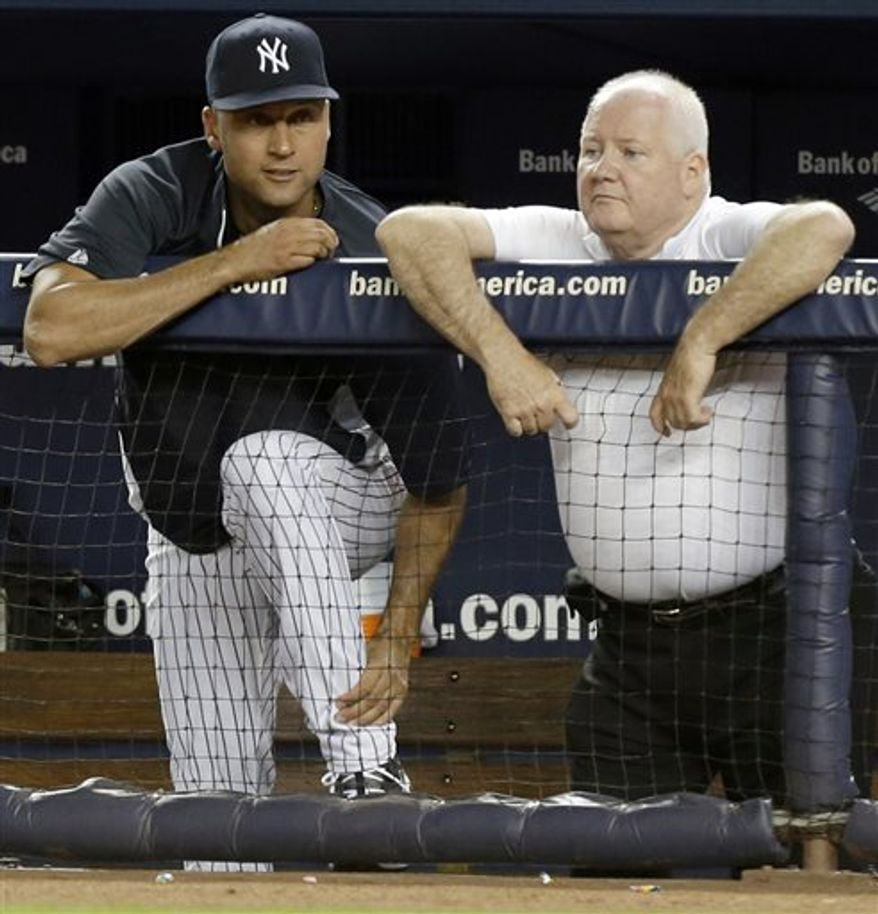 New York Yankees shortstop Derek Jeter, who is on the disabled list after fracturing his left ankle last October, rubs it as he stands beside Yankees trainer Steve Donohue during the seventh inning of an interleague baseball game against the New York Mets at Yankee Stadium in New York, Thursday, May 30, 2013. (AP Photo/Kathy Willens)