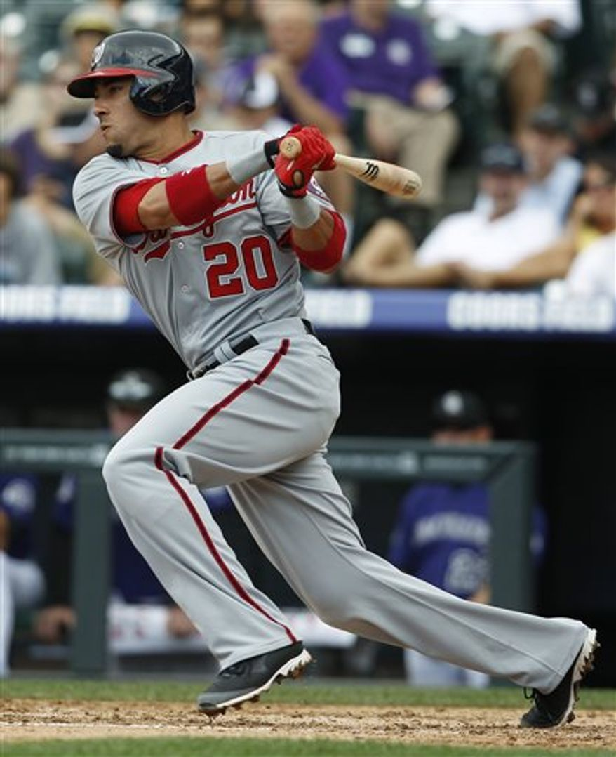 Washington Nationals' Ian Desmond follows the flight of his single against the Colorado Rockies in the fourth inning of a baseball game in Denver, Thursday, June 13, 2013. (AP Photo/David Zalubowski)