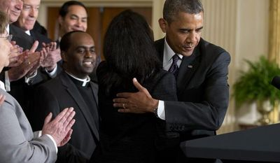** FILE ** President Obama hugs Tolu Olubunmi, an immigration activist, before speaking about immigration reform on June 11, 2013, in the East Room of the White House. (Associated Press)