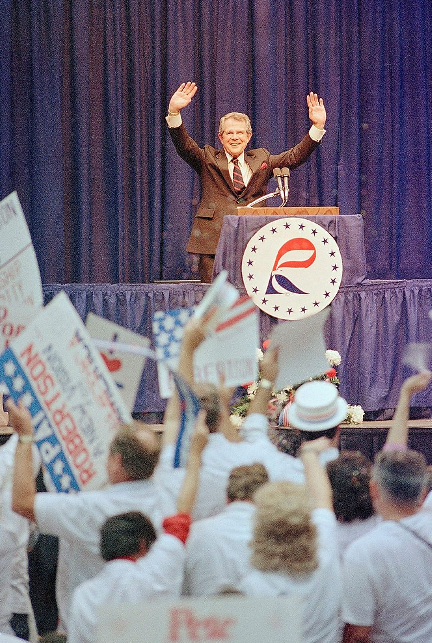 The Rev. Pat Robertson waves in response to cheering supporters after Robertson had finished his remarks at the Republican President Cavalcade of Stars in Ames, Iowa, Saturday, Sept. 12, 1987. (AP Photo/Jeff Davis)