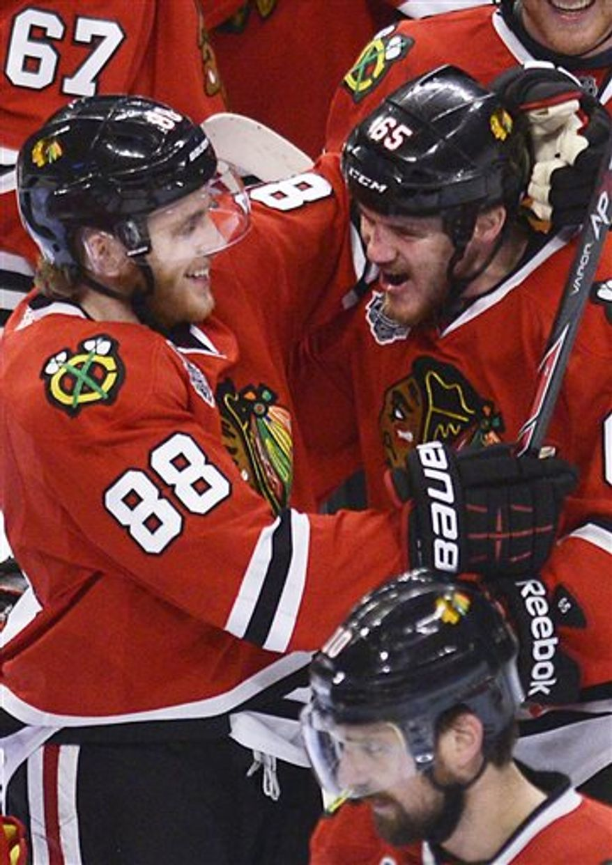 Chicago Blackhawks center Andrew Shaw is hugged by teammate Patrick Kane after Shaw's game-winning goal in the third overtime during Game 1 in the NHL Stanley Cup Final hockey series , Wednesday, June 12, 2013, in Chicago. The Blackhawks won 4-3. (AP Photo/Daily Herald, John Starks)