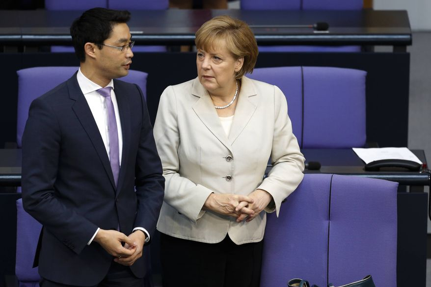German Chancellor Angela Merkel, right, talks to Vice Chancellor and Economic Minister Philipp Roesler during a session of German parliament in Berlin, Germany, Thursday, June 13, 2013. (AP Photo/Markus Schreiber)