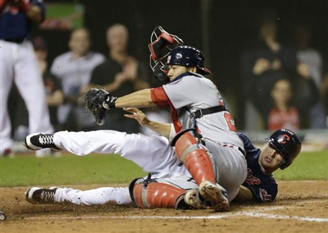 Cleveland Indians' Drew Stubbs, right, scores against Washington Nationals catcher Kurt Suzuki in the ninth inning of a baseball game, Friday, June 14, 2013, in Cleveland. Stubbs scored on a fielder's choice by Jason Kipnis. The Indians won 2-1. (AP Photo/Tony Dejak)