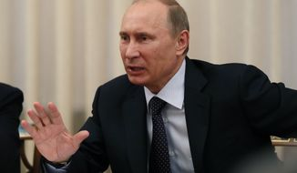Russian President Vladimir Putin speaks at a meeting with representatives of the G-20 Civil Summit at the Novo-Ogaryovo residence outside Moscow on Friday, June 14, 2013. (AP Photo/Yuri Kochertkov, Pool)