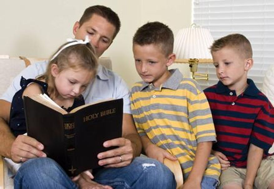 A father reads from the Bible with his children. (Credit: Deseret News)