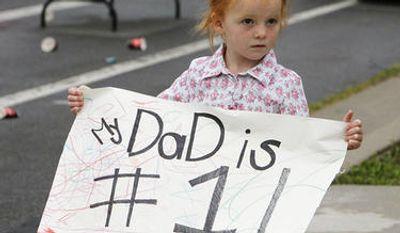 Eliza Gardner holds a sign for her dad during the Deseret News Marathon in Salt Lake City, Tuesday, July 24, 2012. (Ravell Call, Deseret News)