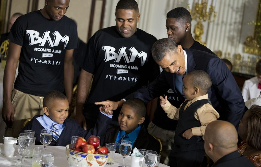 President Obama greets guests, including fathers and their children who participate in the Becoming a Man (BAM) program at Chicago's Hyde Park Academy on Friday, June 14, 2013, in the State Dining Room of the White House in Washington, where the president hosted a Father's Day luncheon. (AP Photo/Evan Vucci)
