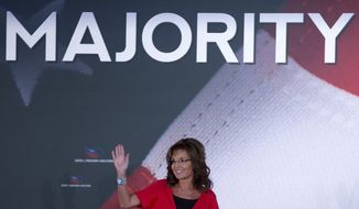 Former Alaska Gov. Sarah Palin waves to the audience during the Faith & Freedom Coalition Road to Majority 2013 conference on Saturday, June 15, 2013, in Washington. (AP Photo/Carolyn Kaster)