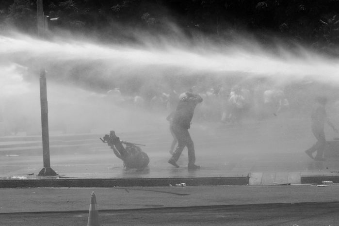A news cameraman (left) falls to the ground as Turkish riot police spray water cannon at demonstrators in the main Kizilay Square in Ankara, Turkey, on Sunday, June 16, 2013. (AP Photo/Burhan Ozbilici)