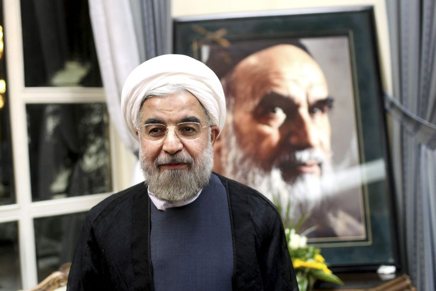 Iranian President-elect Hasan Rowhani stands in front of a portrait of the country's revolutionary founder, Ayatollah Ruhollah Khomeini, during a visit to the late cleric's shrine just outside Tehran on Sunday, June 16, 2013. (AP Photo/Ebrahim Noroozi)