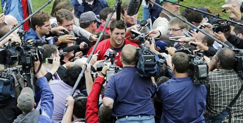 New England Patriots quarterback Tim Tebow is surrounded by reporters and cameramen after NFL football practice in Foxborough, Mass., Tuesday, June 11, 2013. (AP Photo/Charles Krupa)