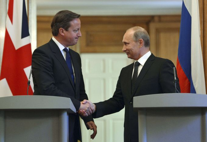 British Prime Minister David Cameron, left, shakes hands with Russian President Vladimir Putin during a press conference at 10 Downing Street in London, Sunday, June 16, 2013. Cameron had talks with Russian President Putin on the Syrian crisis amid fears that differences between Moscow and the West are pushing the two sides toward a new Cold War. (AP Photo/Anthony Devlin)
