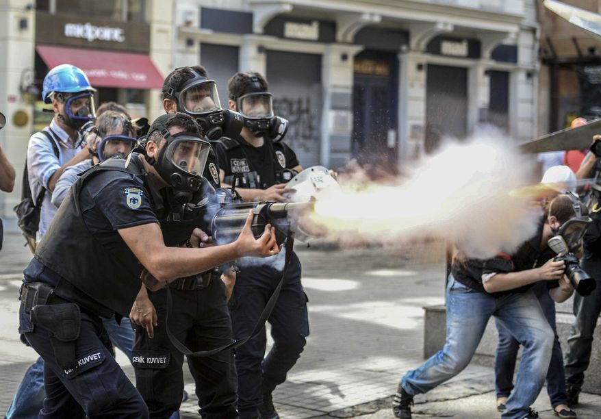 Police fire tear gas as riot police spray water cannon at demonstrators who remained defiant after authorities evicted activists from an Istanbul park, making clear they are taking a hardline against attempts to rekindle protests that have shaken the country, near the city's main Taksim Square in Istanbul, Turkey, Sunday, June 16, 2013. (AP Photo)