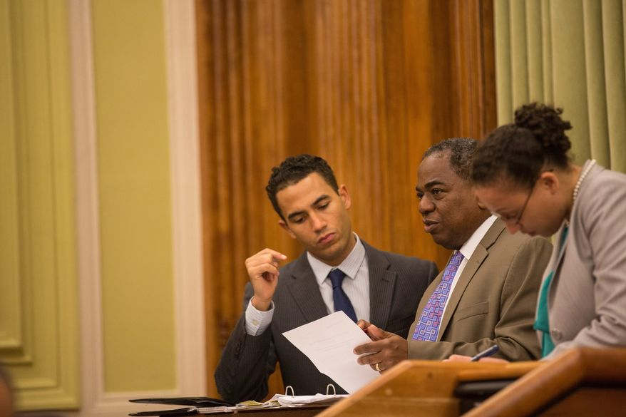 """D.C. Council member Vincent B. Orange (center), at-large Democrat, confers with aides before introducing an emergency amendment to bridge the divide between food trucks and bricks-and-mortar restaurants. """"This represents a fair compromise. Hopefully we can put this to bed after many years of working on this,"""" he said. (Andrew S. Geraci, The Washington Times)"""