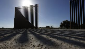 **FILE** The sun casts a shadow on the border fence that passes through the Nature Conservancy's southernmost preserve in Brownsville, Texas, on Sept. 4, 2012. (Associated Press)