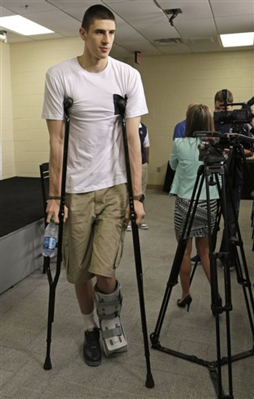 Maryland's Alex Len leaves a media interview on crutches during a pre-draft visit to the NBA Charlotte Bobcats basketball team in Charlotte, N.C., Tuesday, June 18, 2013. The NBA Draft begins June 27. (AP Photo/Chuck Burton)