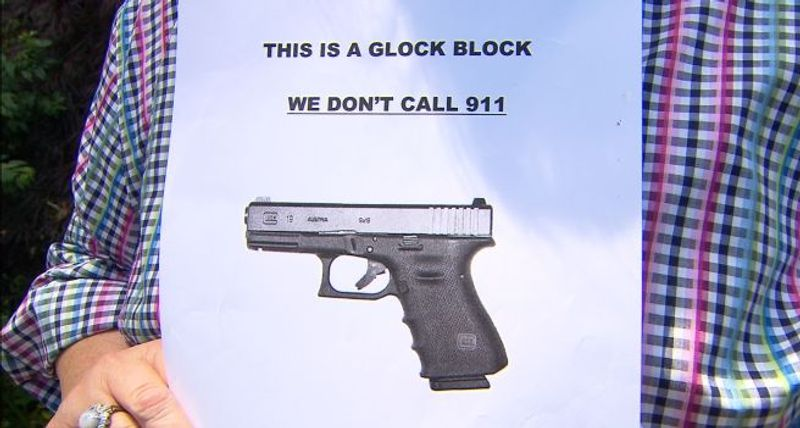 """Milwaukie, Ore., resident Coy Toloman holds up one of the new signs going up in her """"Glock block."""" (Credit: KOIN 6 News, Ellen Hansen)"""