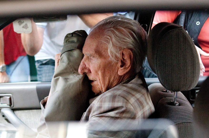 ** FILE ** In this Wednesday, July 18, 2012, file photo, alleged Hungarian war criminal Laszlo Csatary sits in a car as he leaves the Budapest Prosecutor's Office after he was questioned by detectives on charges of war crimes during WWII and prosecutors ordered his house arrest in Budapest, Hungary. (AP Photo/MTI, Bea Kallos, File)
