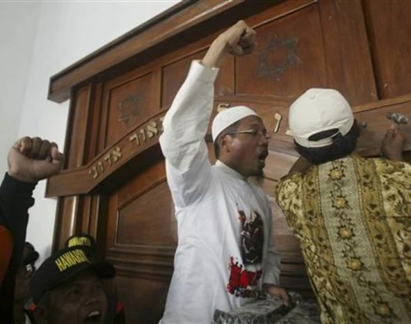 ** FILE ** A Muslim man vandalizes the door ornament of a synagogue during a rally against Israel in East Java, Indonesia, Friday, June 4, 2010. (Associated Press)