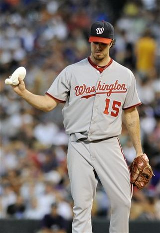 Washington Nationals starting pitcher Dan Haren tosses down the rosin bag after giving up five runs in the fifth inning of a baseball game against the Colorado Rockies on Tuesday, June 11, 2013 in Denver. (AP Photo/Chris Schneider)