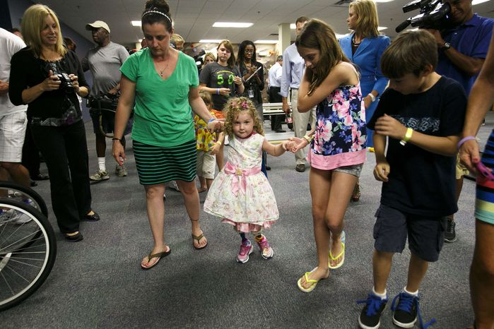 Ireland Nugent, 2, walks on her prosthetic legs while holding on to her mother, Nicole's, and sister, Italia Nesbitt, 11, right, hands at Prosthetic and Orthotic Associates in Orlando on Monday, June 17, 2013. Ireland lost both feet in a lawn mower accident. (AP Photo/The Tampa Bay Times, Will Vragovic)