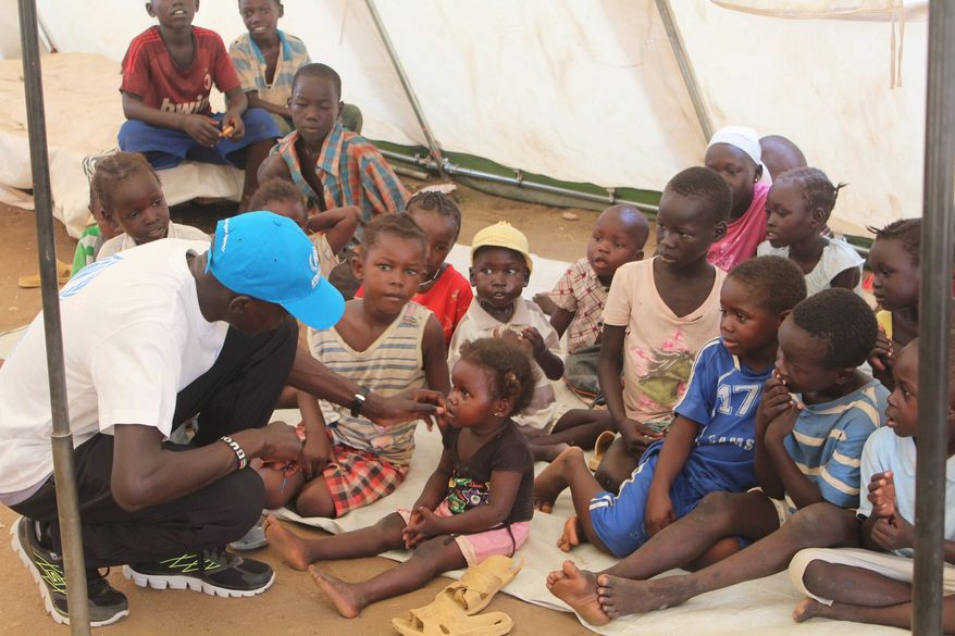The former Lost Boy of Sudan meets with a group of toddlers who have better prospects but still many struggles ahead. (Photograph provided by U.N. High Commissioner for Refugees)