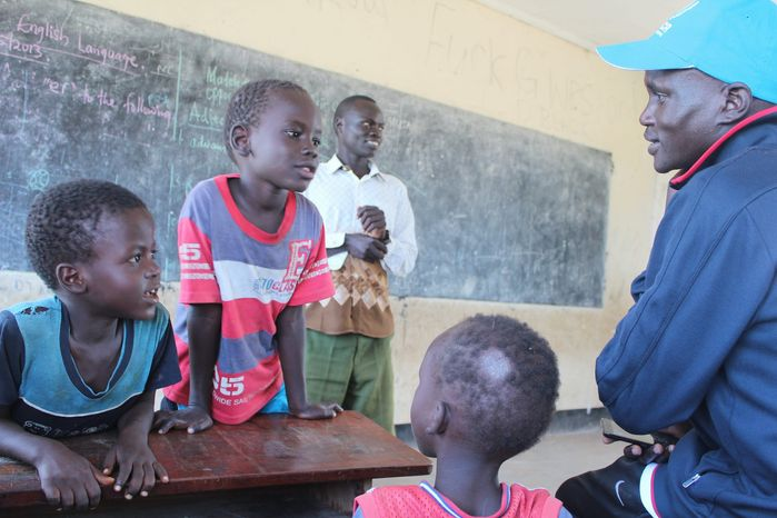 At a U.N.-sponsored school, Guor Mading meets with pupils who are curious about his improbable story of escaping the horrors of war and becoming an Olympic runner. (Photograph provided by U.N. High Commissioner for Refugees)