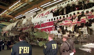 **FILE** FBI agents and New York state police guard the reconstruction of TWA Flight 800 in Calverton, N.Y., on Nov. 19, 1997. Flight 800 exploded and crashed July 17, 1996, while flying from New York to Paris, killing all 230 people aboard. An FBI investigation has concluded that there is no evidence that the crash was the result of a criminal act. (Associated Press)