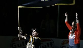 "Richard Donohue, the Massachusetts Bay Transportation Authority officer wounded during the shootout with the Boston Marathon bombing suspects, waves a ""Boston Strong"" banner as his wife, Kimberly, raises her arms during ceremonies prior to Game 3 of the Eastern Conference finals in the NHL hockey Stanley Cup playoffs between the Boston Bruins and the Pittsburgh Penguins, in Boston on Wednesday, June 5, 2013. (AP Photo/Elise Amendola)"