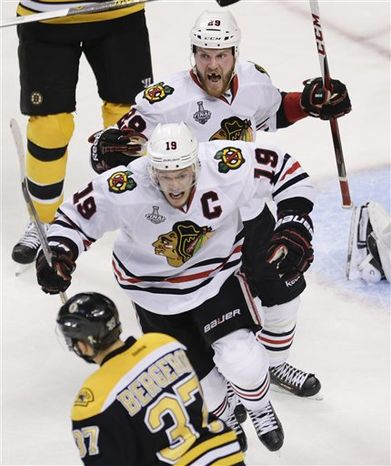 Chicago Blackhawks left wing Bryan Bickell (29) and center Jonathan Toews (19) celebrate the winning goal by Brent Seabrook, not shown, in front of Boston Bruins center Patrice Bergeron (37) during the first overtime period in Game 4 of the NHL hockey Stanley Cup Finals, Wednesday, June 19, 2013, in Boston. Chicago won 6-5. (AP Photo/Charles Krupa)