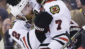 Chicago Blackhawks defenseman Brent Seabrook (7) celebrates his game-winning goal against the Boston Bruins with defenseman Duncan Keith (2) during the first overtime period in Game 4 of the NHL hockey Stanley Cup Finals, Wednesday, June 19, 2013, in Boston. Chicago won 6-5. (AP Photo/Elise Amendola)