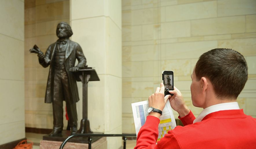 Capitol visitors tour guide Dan Pearson takes a photograph of a statue of Frederick Douglass before a congressional ceremony to commemorate the dedication and unveiling of the statue in Emancipation Hall of the the United States Visitors Center, Washington, D.C., Wednesday, June 19, 2013. (Andrew Harnik/The Washington Times) **FILE**