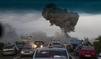 In this photo taken late Tuesday, June 18, 2013, a traffic jam forms on a highway blocked because of a fire at a military depot near Chapaevsk in the Samara region of southern Russia. (AP Photo/Anatoly Bazhukov)