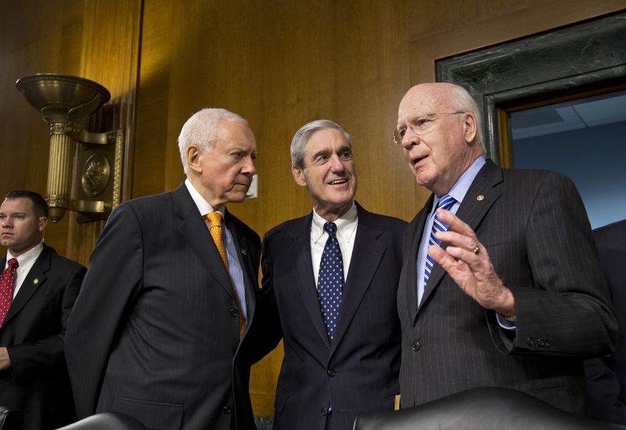 Senate Judiciary Committee Chairman Patrick Leahy (right), Vermont Democrat, and committee member Sen. Orrin Hatch (left), Utah Republican, greet FBI Director Robert Mueller on Capitol Hill on June 19, 2013, prior to the start of the committee's hearing on national security matters. Mueller is nearing the end of his 12 years as head of the law enforcement agency. (Associated Press)