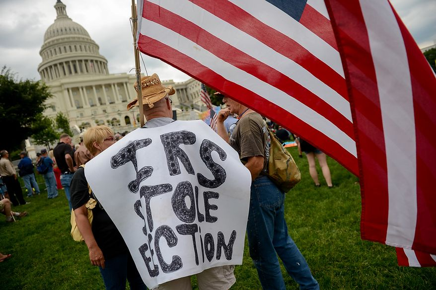 """Gene Mcilhone [cq], of Valley Forge, Penn. wears a sign that reads, """"I.R.S. Stole Election"""" at a tea party rally against the Internal Revenue Service entitled, """"Audit the IRS"""" on the West Lawn of the U.S. Capitol Building, Washington, D.C., Wednesday, June 19, 2013. (Andrew Harnik/The Washington Times)"""