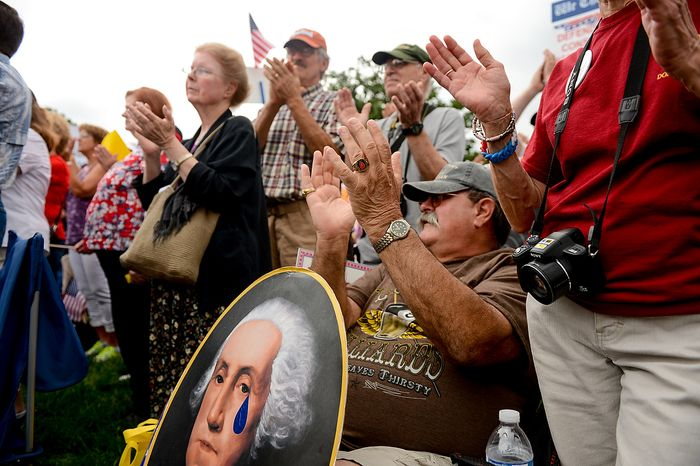 """David Grimm, of Pittsburg, Pa. holds a poster depicting George Washington with a teardrop, applauds for speakers during a tea party rally against the Internal Revenue Service entitled, """"Audit the IRS"""" on the West Lawn of the U.S. Capitol Building, Washington, D.C., Wednesday, June 19, 2013. (Andrew Harnik/The Washington Times)"""